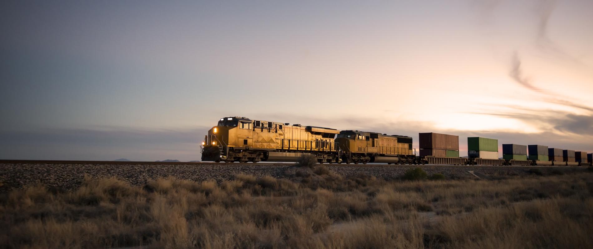 Locomotive rolling through plains at sunset